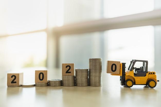 Feche acima do caminhão de empilhadeira do brinquedo que carrega o bloco de madeira do número 0 à parte superior da pilha de moedas.