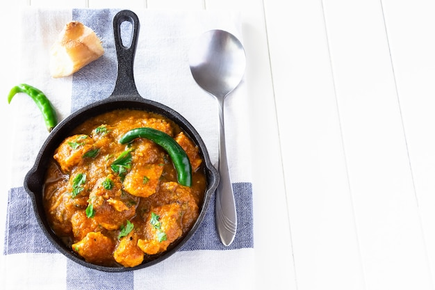 Feche acima do caril e do limão indianos tradicionais da galinha da manteiga servidos com pão do chapati no ferro-molde. vista do topo. espaço da cópia