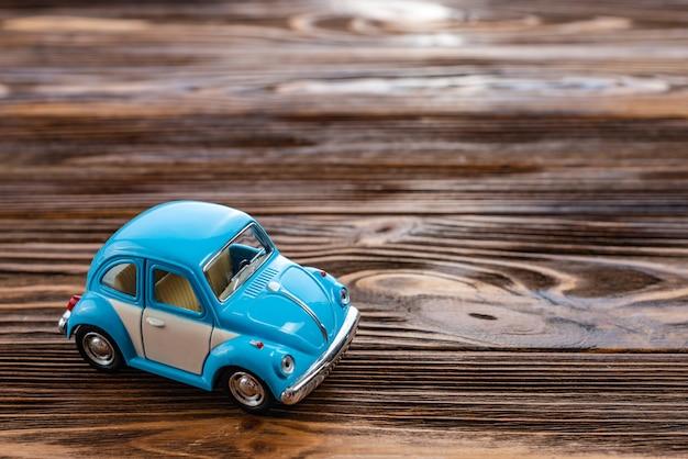 Feche acima do carro do brinquedo em um fundo de madeira.