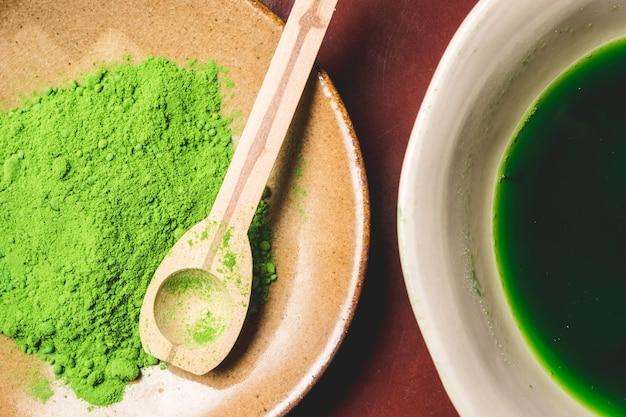 Feche acima do chá de matcha e do verde pulverizado.