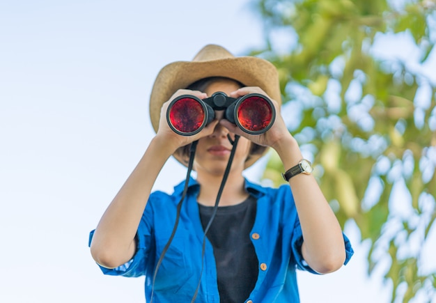 Feche acima do chapéu do desgaste de mulher e segure binocular no campo de grama