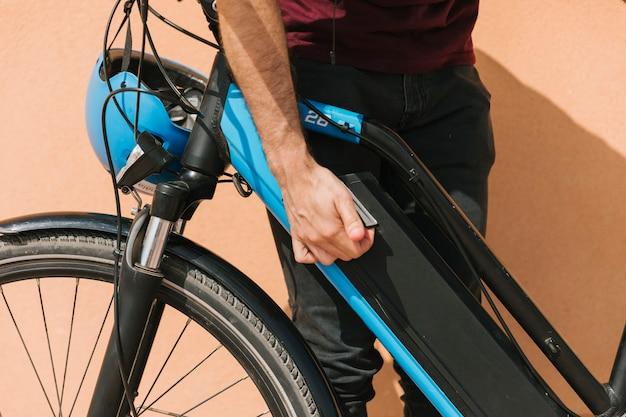 Feche acima do ciclista que fixa a bateria da e-bicicleta