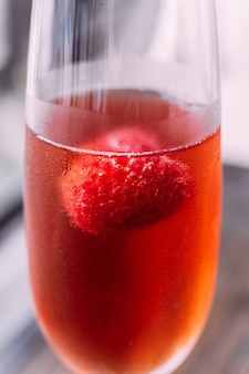 Feche acima do cocktail vermelho com framboesa para dentro no vinho de vidro.