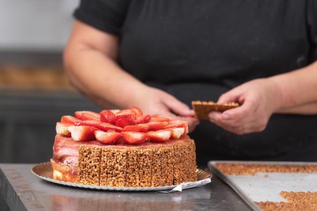 Feche acima do confeiteiro profissional que faz um bolo delicioso na loja de pastelaria.