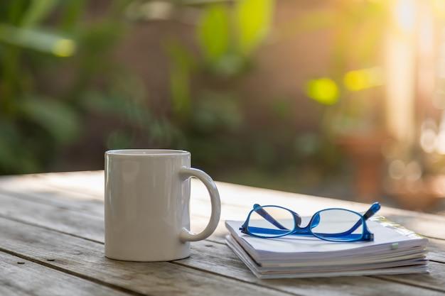 Feche acima do copo branco da caneca de café quente com livro e vidros de leitura na tabela de madeira no jardim com espaço da cópia.