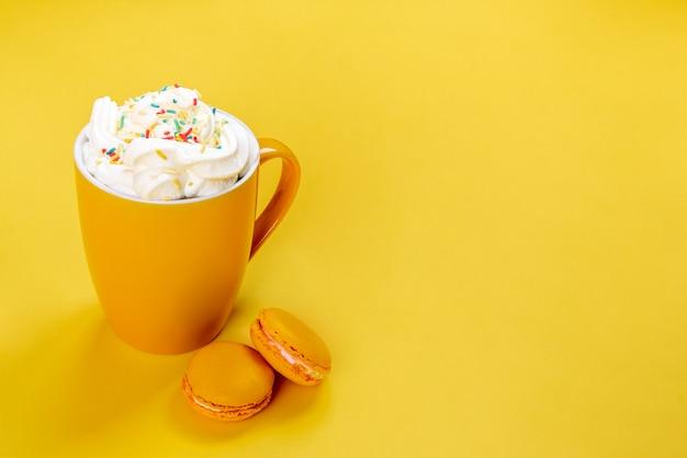 Feche acima do copo de café amarelo e dos bolinhos de amêndoa franceses no fundo amarelo.