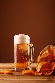 Feche acima do copo de cerveja e batatas fritas sobre marrom