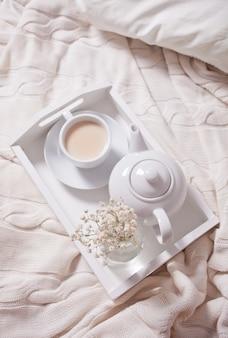 Feche acima do copo do chá, do leite, do bule e do ramalhete das flores brancas na bandeja branca.