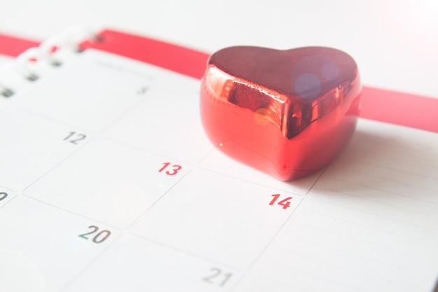 Feche acima do coração vermelho e numere no calendário, conceito do valentim