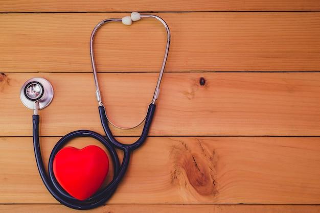 Feche acima do coração vermelho e steythoscope na tabela de madeira velha
