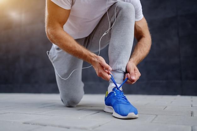 Feche acima do desportista caucasiano no fato de esporte que amarra o laço ao ajoelhar-se ao ar livre.