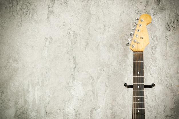 Feche acima do detalhe de uma guitarra da ligação elétrica com fundo velho da parede de tijolo.