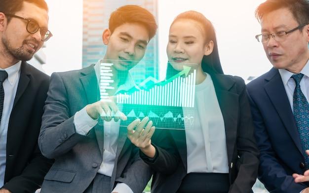 Feche acima do empresário e empresária apresentando gráficos digitais.