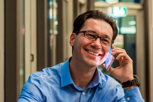 Feche acima do empresário sorrindo usando o telefone inteligente moderno, jovem feliz trabalhando em seu escritório e segurando celular