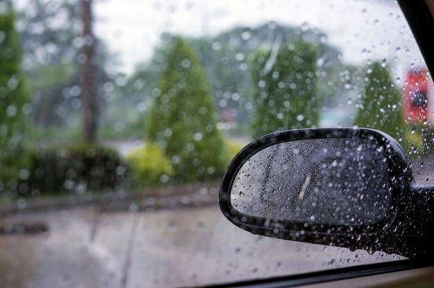 Feche acima do espelho de asa no carro no dia chovendo.