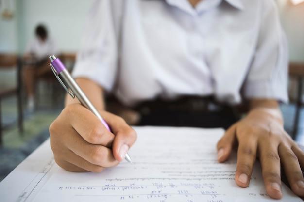 Feche acima do estudante que lê e que escreve o exame com esforço na sala de aula.