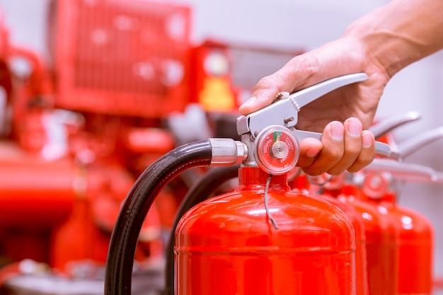 Feche acima do extintor de incêndio e do pino puxando no tanque vermelho.