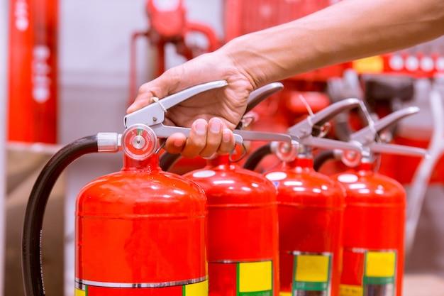 Feche acima do extintor de incêndio e puxando o pino no tanque vermelho.