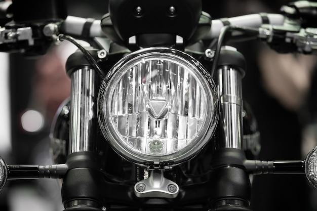 Feche acima do farol da motocicleta moderna na noite.
