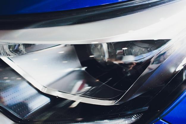 Feche acima do farol do tiro no carro azul luxuoso. conceito de carro esporte moderno e caro
