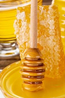 Feche acima do favo de mel com dipper