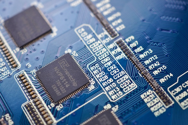 Feche acima do fundo azul eletrônico dos componentes eletrônicos de placa de circuito.