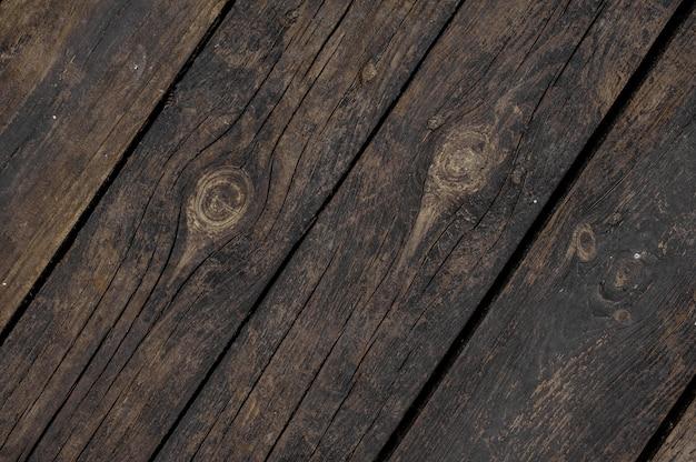 Feche acima do fundo da textura de velhas tábuas de madeira escuras, dispostas obliquamente no chão