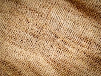 Feche acima do fundo marrom da textura do pano de saco. foco suave