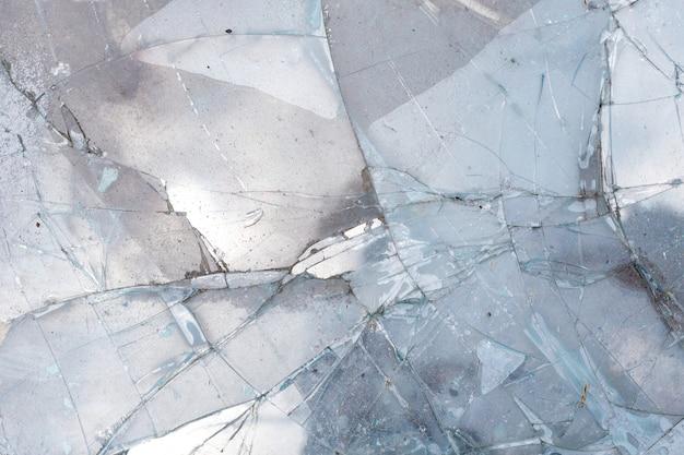 Feche acima do fundo rachado quebrado vidro da textura do espelho, acidente caem para baixo.