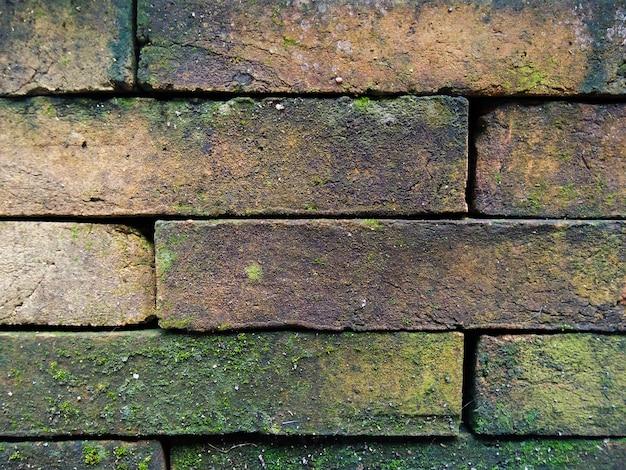 Feche acima do fundo velho da parede de alvenaria