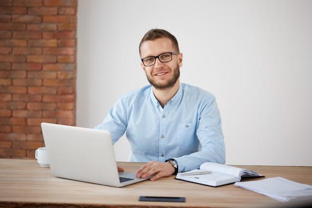 Feche acima do gerente masculino barbudo adulto alegre nos vidros e na camisa clássica que sentam-se na mesa no escritório, trabalhando no computador pessoal, escrevendo a informação no caderno.