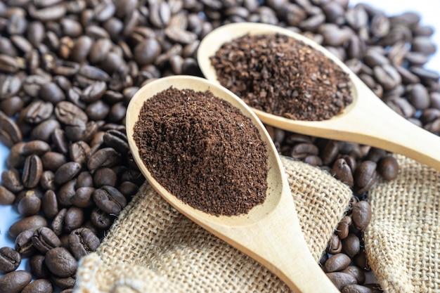 Feche acima do grão de café esmagado no tamanho fino na colher de madeira com os feijões de café no fundo