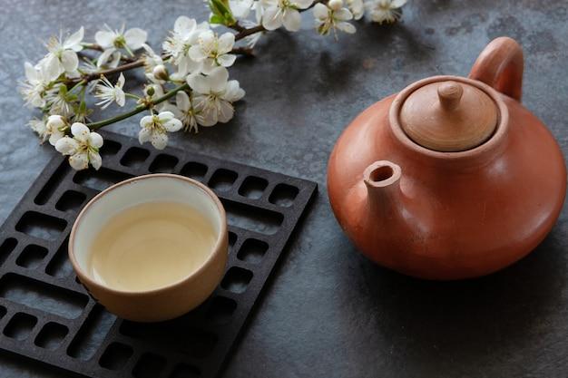 Feche acima do grupo de chá asiático cerâmico com chá verde de japão com ramos de florescência da cereja na tabela cinzenta.