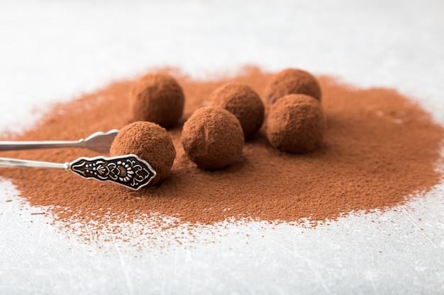 Feche acima do grupo de trufas de chocolate pretas apetitosas cobertas na poeira de cacau. profundidade superficial de campo.