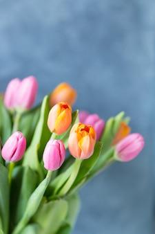 Feche acima do grupo fresco do ramalhete de tulipas alaranjadas da rosa do rosa no vaso. copie o espaço. fundo floral cartão postal. foco seletivo.