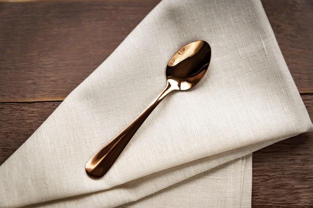 Feche acima do guardanapo bege de matéria têxtil e serviu a colher do chá na tabela de madeira.