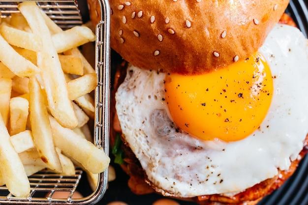 Feche acima do hamburguer saboroso com o ovo frito servido com fritadas na placa preta na tabela de madeira.