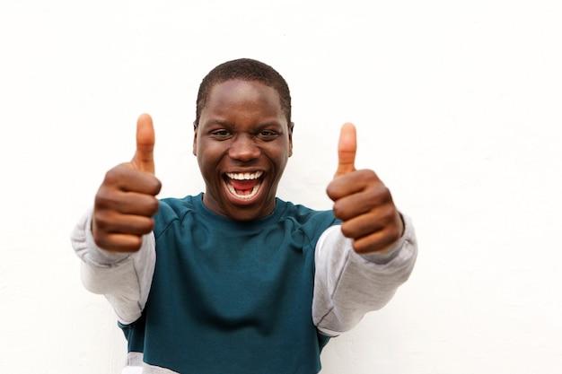 Feche acima do homem africano alegre que mostra os polegares acima com as duas mãos no fundo branco
