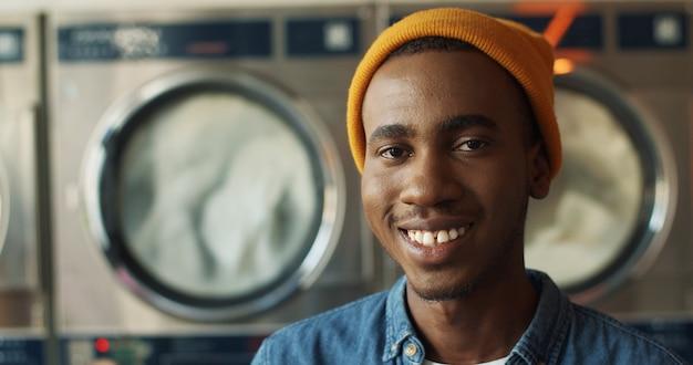 Feche acima do homem afro-americano novo considerável no chapéu amarelo que sorri alegremente à câmera na sala de serviço da lavanderia. retrato do indivíduo feliz que ri com as máquinas de lavar no fundo.