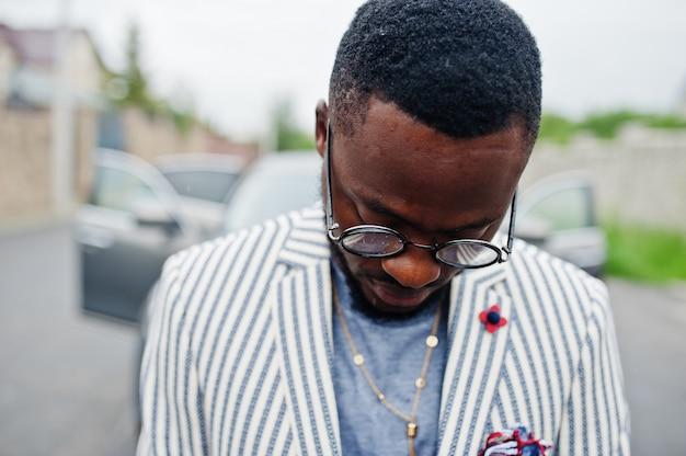 Feche acima do homem afro-americano rico e elegante no blazer e óculos colocados contra carro suv.