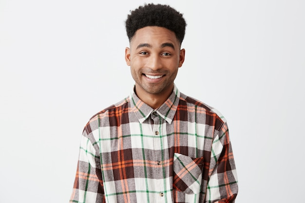 Feche acima do homem americano alegre de pele escura bonito novo com cabelo preto encaracolado na camisa quadriculado que sorri com dentes com expressão feliz e relaxada da cara.
