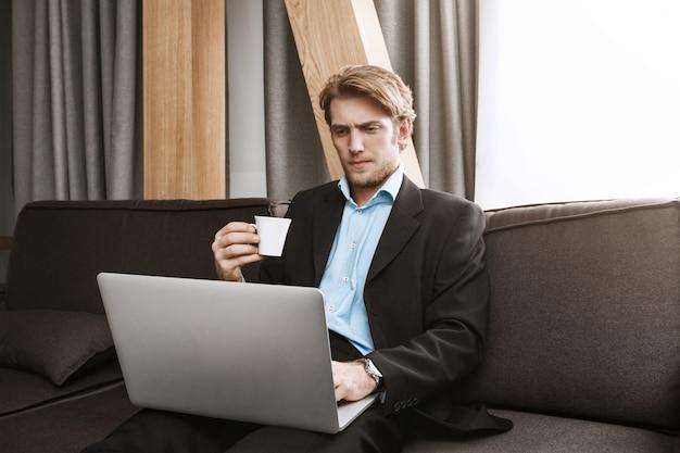 Feche acima do homem com barba elegante que bebe o café, olhando no monitor do portátil com expressão séria e insatisfeita, trabalhando em casa.