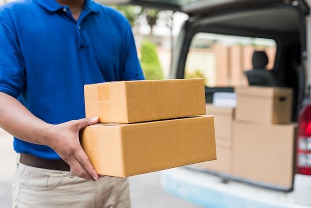 Feche acima do homem de entrega nos uniformes azuis que guardam a caixa de cartão do pacote.