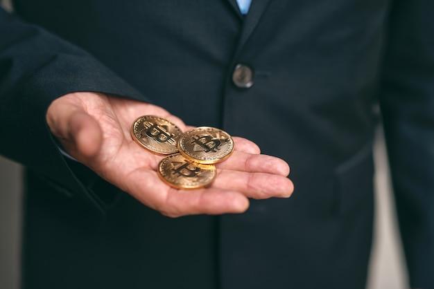 Feche acima do homem de negócios adulto superior que mantém bit-moedas disponivel.