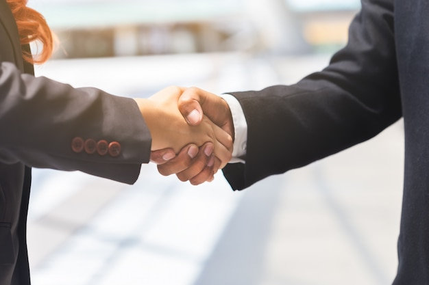 Feche acima do homem de negócios e aperto de mão da mulher de negócios para o sócio, conceito do negócio.