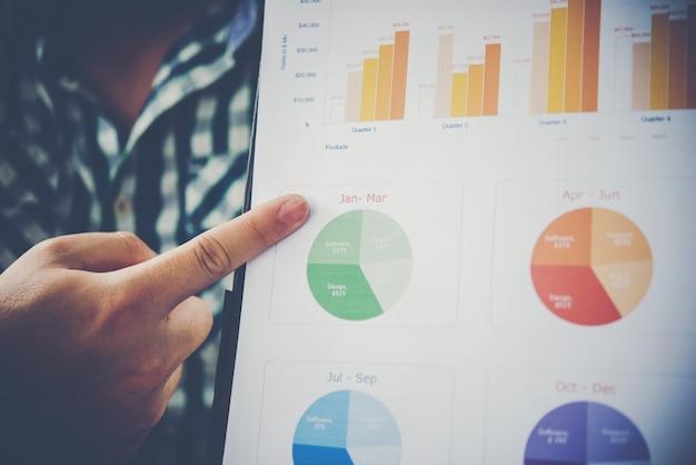 Feche acima do homem de negócios em uma reunião ou uma mão da apresentação apontando com o documento da tabela do negócio na tabela.