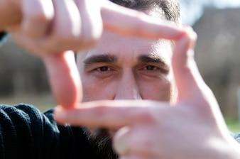 Feche acima do homem de negócios lindo, olhando a câmera ao fazer um gesto do quadro da mão.