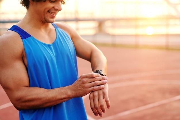 Feche acima do homem desportivo que ajusta o relógio esperto ao estar na corte na manhã.