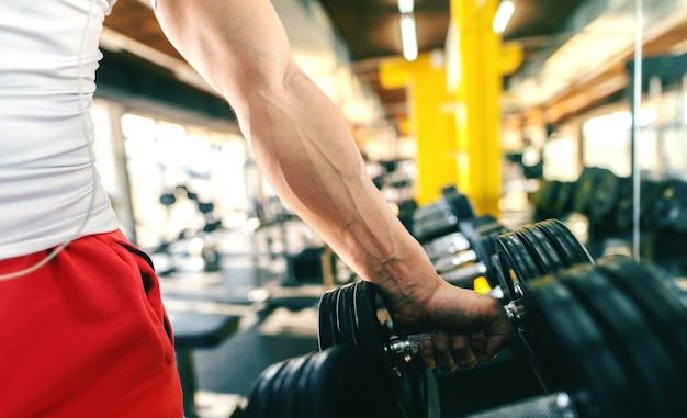 Feche acima do homem escolher halteres em pé no ginásio.