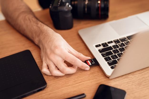 Feche acima do homem farpado do freelancer que usa o cartão de memória.